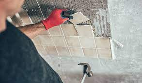 Man removing tile from wall wearing safety gloves